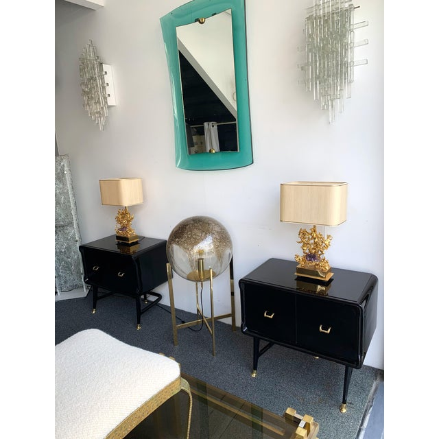 Pair of black lacquered wood nightstands, side end low tables, brass feet and handle, typical feet by the Italian designer...