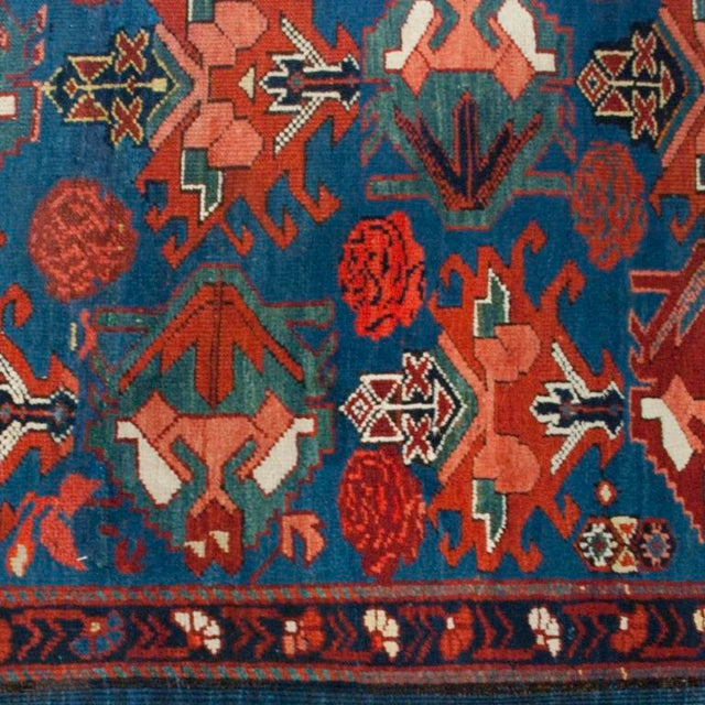 An early 20th century Caucasian carpet with unbelievable crimson, salmon and indigo colors, with a floral and geometric...
