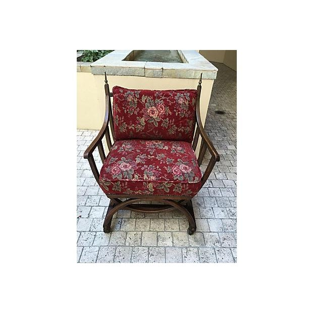 A delightful unusual barrel chair on casters. This piece features brass finials, brass tacks, and original floral upholstery.