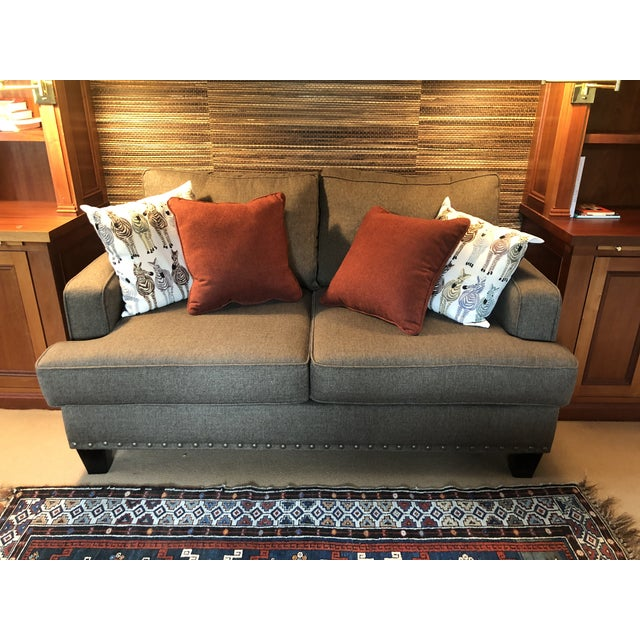 A handsome versatile medium sized custom sofa or loveseat upholstered richly in a brownish taupey olive fabric, having two...