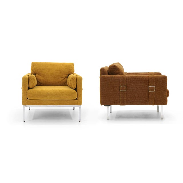 All original pair of Milo Baughman lounge / club chairs with belt buckle detail upholstery. Complimenting colors in the...