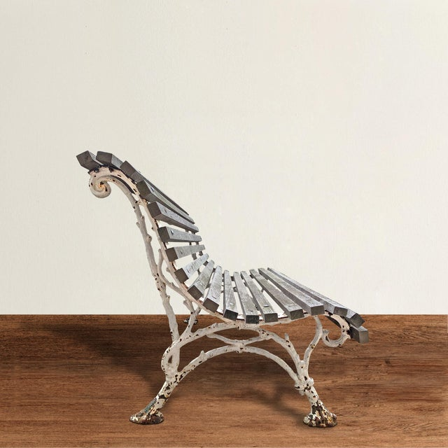 A whimsical turn-of-the-20th century Parisian cast iron garden bench with sculptural faux bois style legs and newer teak...