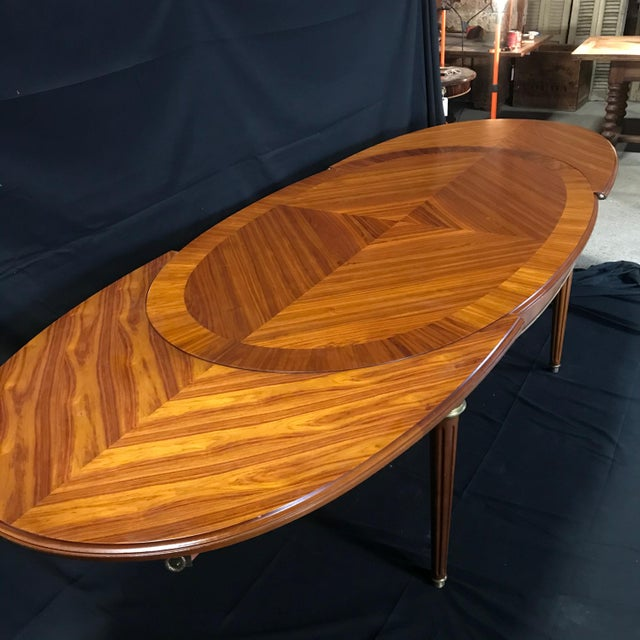 This Louis XVI style oval dining table is made out of beautiful banded and inlaid fruitwood with a lacquered finish....