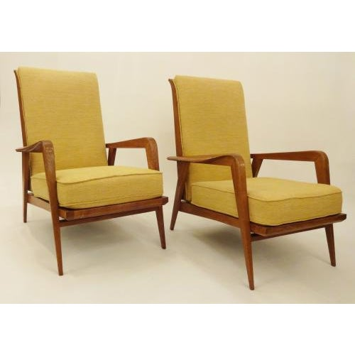 Etienne Henri Martin Pair of modernist lounge chairs each featuring frames in waxed Oak with curving carved armrests,...