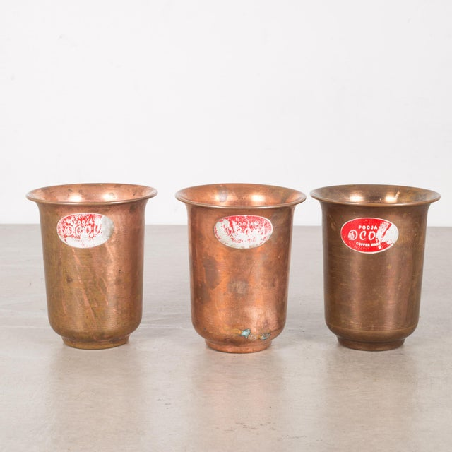 ABOUT A set of six copper ware picnic cups with original labels. CREATOR Pooja Copperware. DATE OF MANUFACTURE c.1950s....