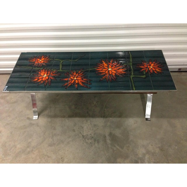Abstract painted ceramic tile table using bold color and raised glaze. Floral design in oranges on green and blue field....