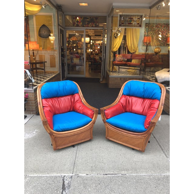 Stunning pair of mid century rattan and bamboo swivel lounge chair for outdoor patio with brand new blue & red cushions....