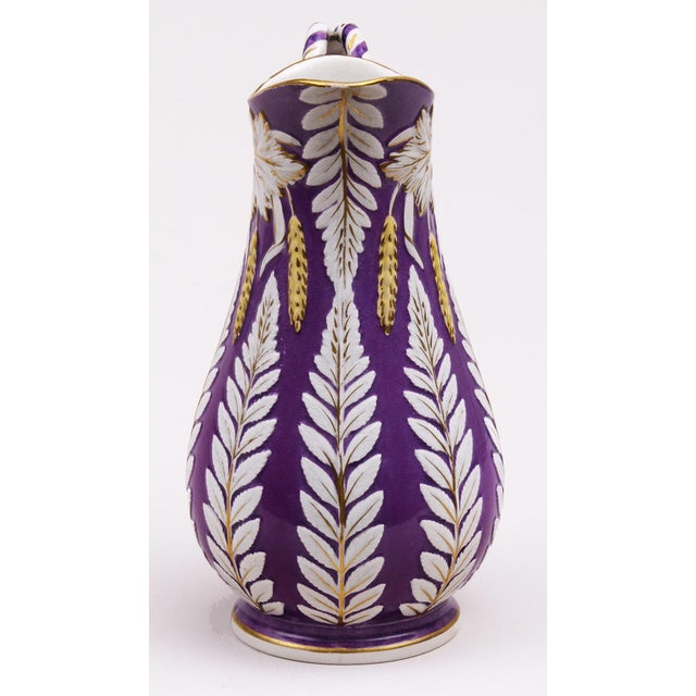 Pottery fuchsia-colored jug by William Brownfield with a rope handle and decorated with leaf patterns, wheat and gilding....