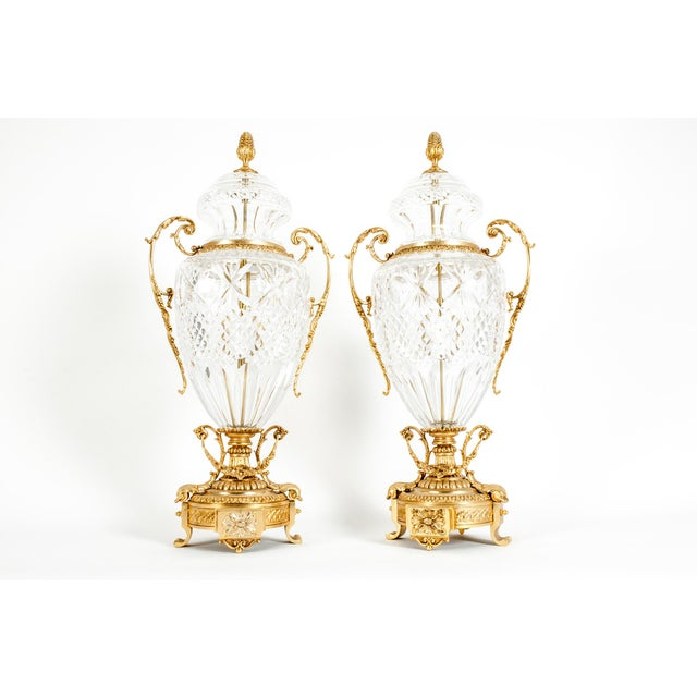 Impressive pair of footed gilt bronze-mounted diamond shape cut crystal decorative urns / centerpiece. Each urn is mounted...