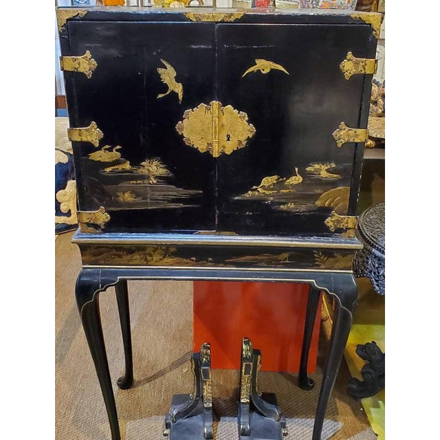 Antique Asian tea cabinet on matching stand. A rectangular cabinet with two hinged doors decorated with landscapes in gold...