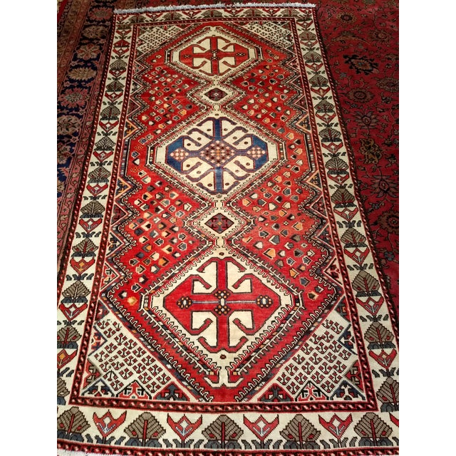 The Shiraz carpet from western Persia has a red field. Three medallions are set in the field with the colors of ivory,...