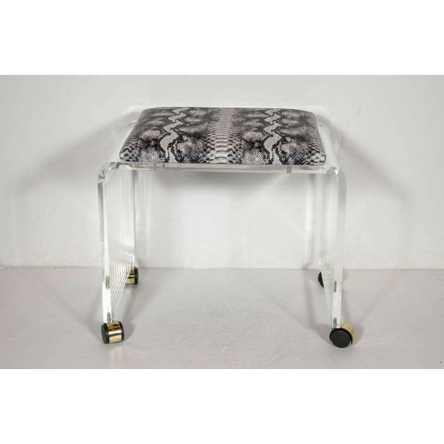 Chic Mid-Century Modernist clear Lucite bench or vanity stool in a waterfall design on chrome castors. The top cushion has...