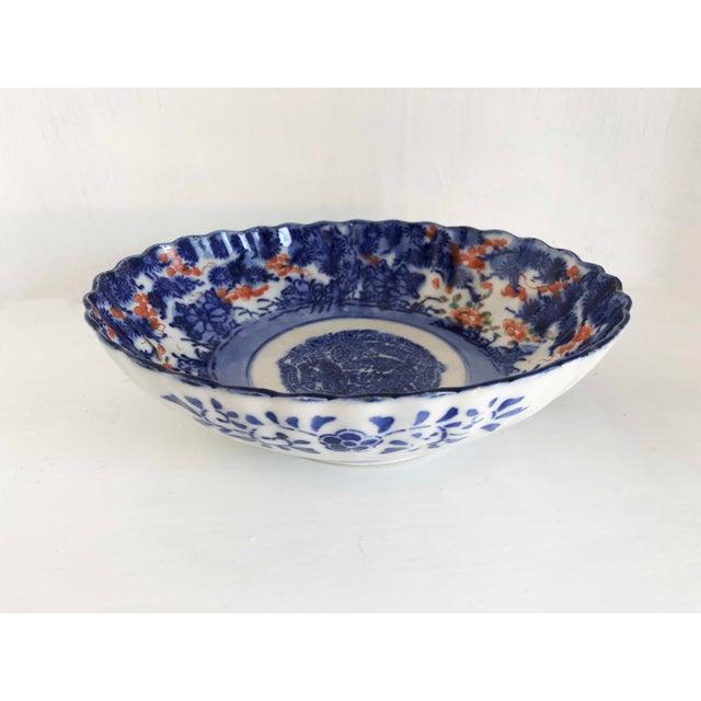 Deep blue center design with imperfect center circle. Floral design on underside of dish. Bands around bottom pedestal not...