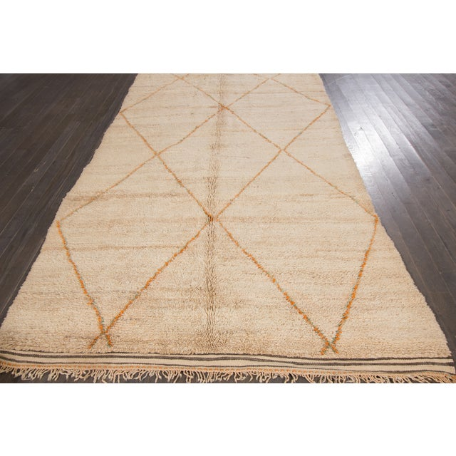 A hand-knotted Moroccan rug with a geometric design on a beige field. This rug has magnificent detailing and is ready for...