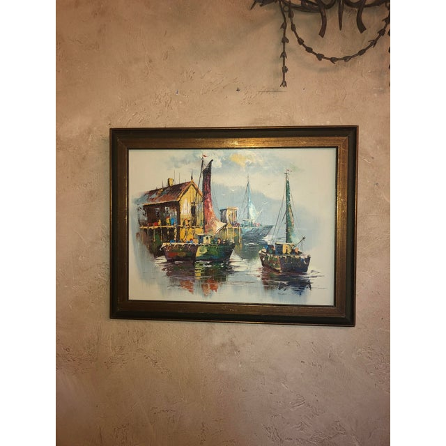 A peaceful yet colorful mid century painting of sailboats near the boathouse. In a dark wood frame.