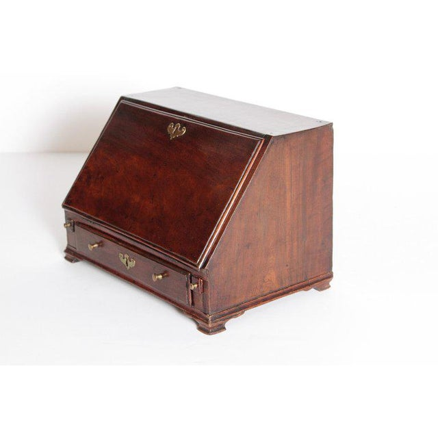 A Georgian mahogany miniature secretary with a fall front opening. The fitted interior has pigeon holes and drawers,...