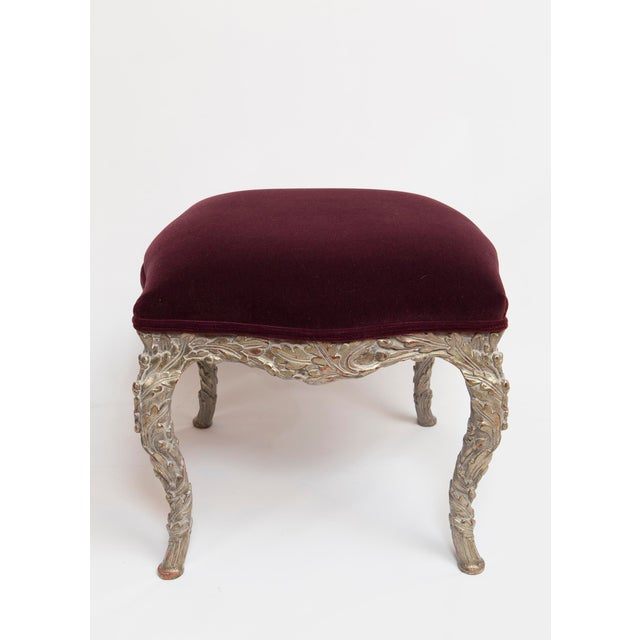 Pair of wood carved stools upholstered in burgundy mohair velvet fabric. The pair of stools are finished in a distressed...