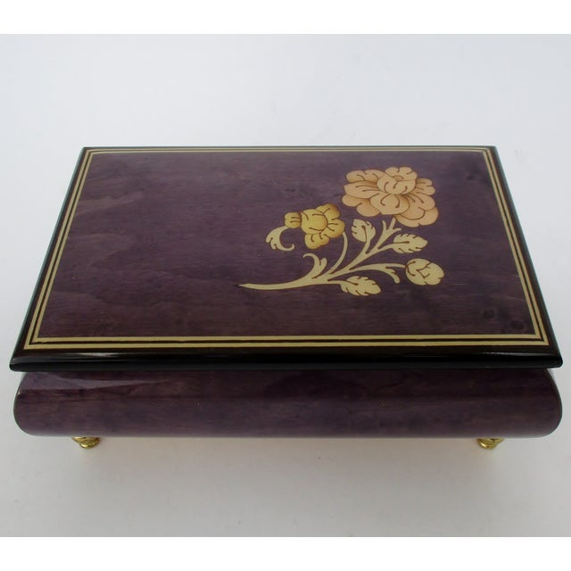 Italian music box in violet-tinted lacquered glaze, accented with a gold-glazed wood inlaid flower and gold metal feet....