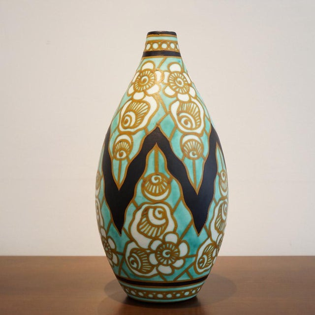 This is an earthenware vase with polychrome design and stylized floral motifs. Franco-Belgian ceramist Charles Catteau...