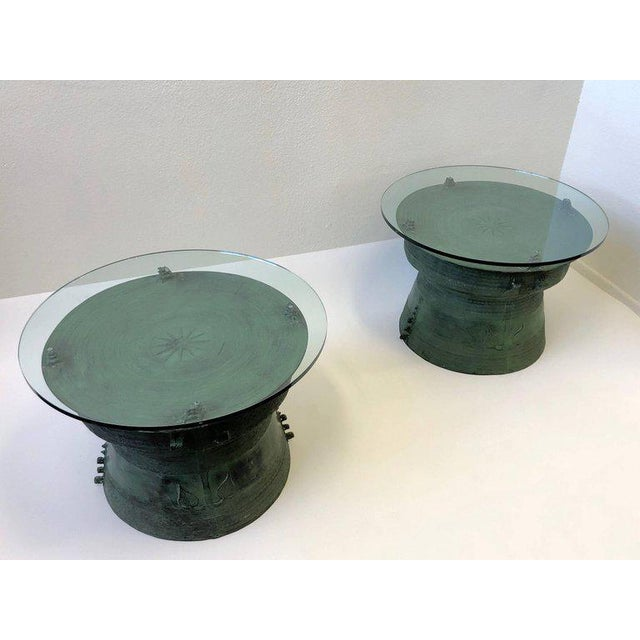 An amazing pair of cast bronze with glass tops, south Asian rain drum side table. The tables have a beautiful aged patina...