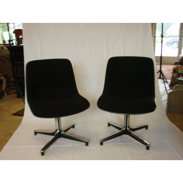 Two attractively-shaped chairs. Black with black upholstery on chrome four-point star bases, by GF Office Equipment....