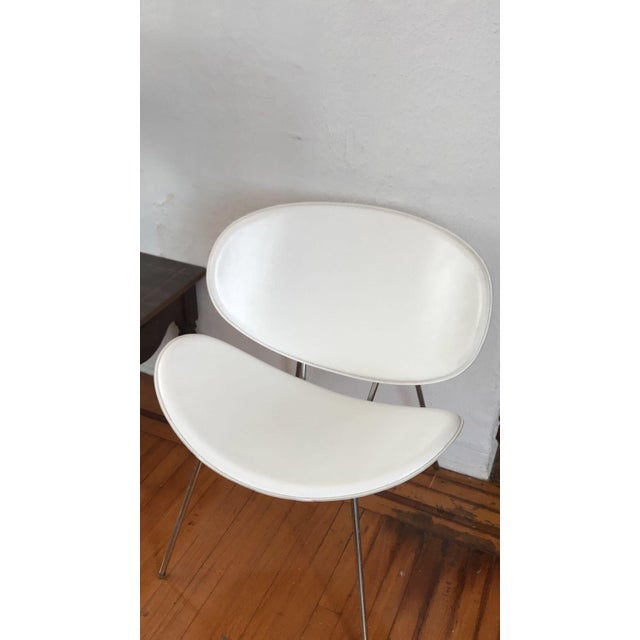 Two original white leather clam shell chairs