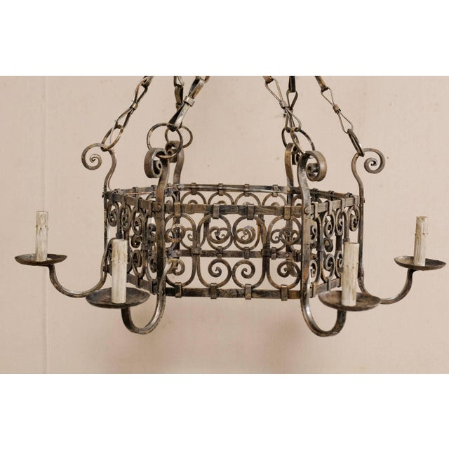 A French midcentury six-light iron chandelier. This lovely French chandelier from the mid-20th century has a rounded...