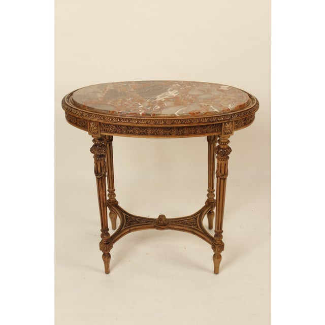 Louis XVI style carved occasional table with marble top, circa 1930. This table has excellent quality hand carved...