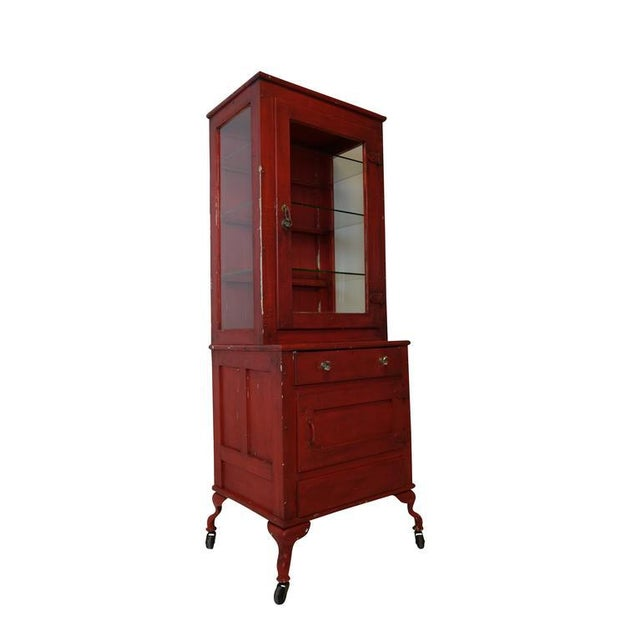 This is a unique red painted medical cabinet with cabriole legs on casters. The set back three-sided glass display has the...