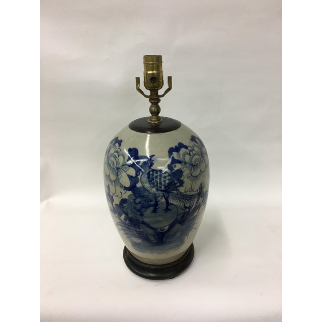 Vintage ceramic ginger jar lamp made with blue and white Chinese porcelain. Traditional floral painting design decorates...