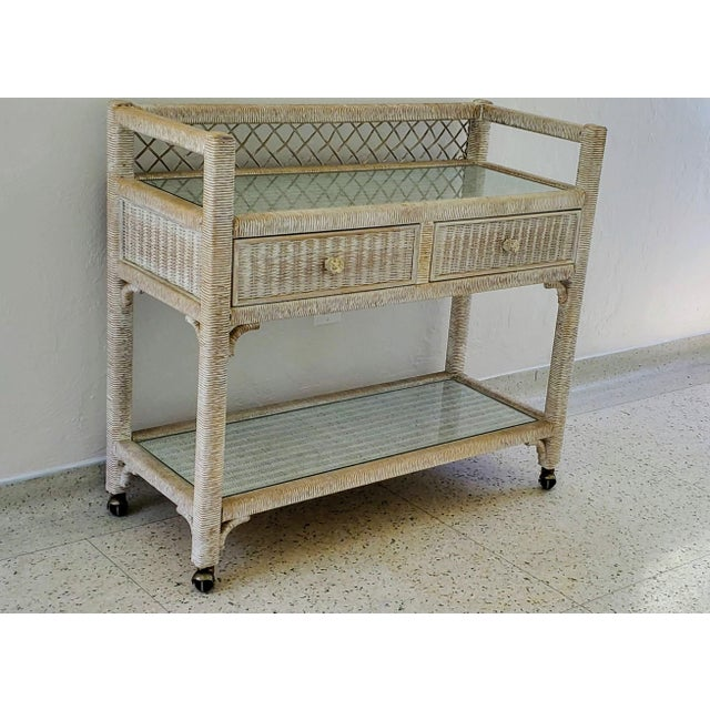 Vintage Henry Link wicker rolling bar cart. Two drawers. Two shelves with glass panes. Has casters.