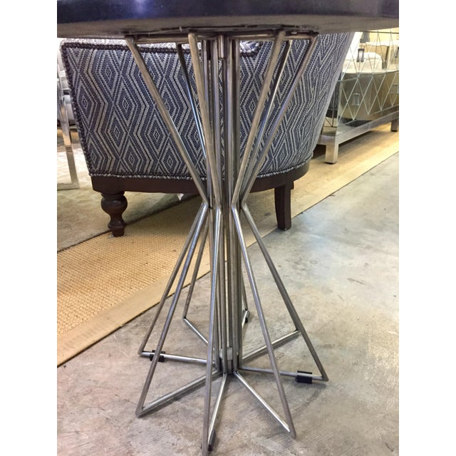 This beautiful contemporary Industrial Table sits in steel legs. Features round granite black top.