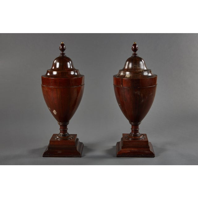 A rare pair of large walnut late 18th century English wine coolers, their square molded bases supporting chalice form...