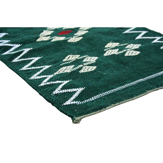 Handwoven Moroccan Berber kilim with a design of natural symbols and geometric shapes.