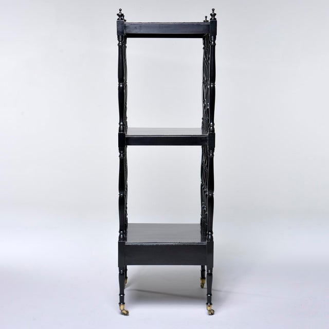Circa 1930s English mahogany etagere with new ebonised finish. This piece features original brass casters, a functional...