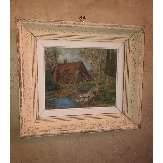 A vintage French landscape oil painting with a thatched roof cottage in the woods near a stream. In a distressed wooden...