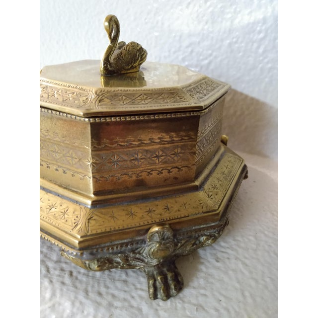 This Brass Swan Finial Paw Feet Trinket Box has an octagon shape with ornate intaglio designs on the outside. The swan...