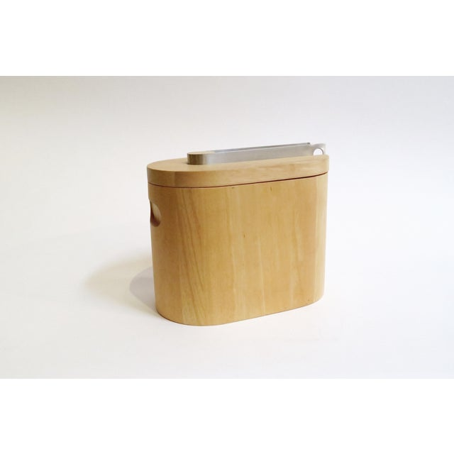 Wooden Ice Bucket. Plastic interior. Steel ice tongs rest in nook on top.