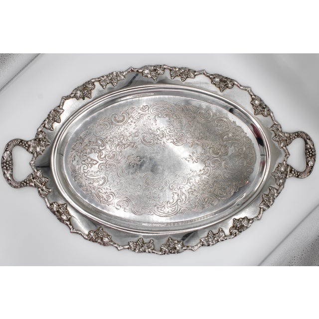 A lovely mid-20 century silver plate oval handled serving tray with grapevine motif and ornate scrolled engravings.