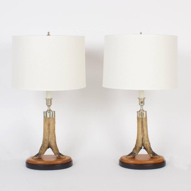 Vintage pair of custom English deer hoof table lamps with silver plated candle cups and hardware, presented on custom...