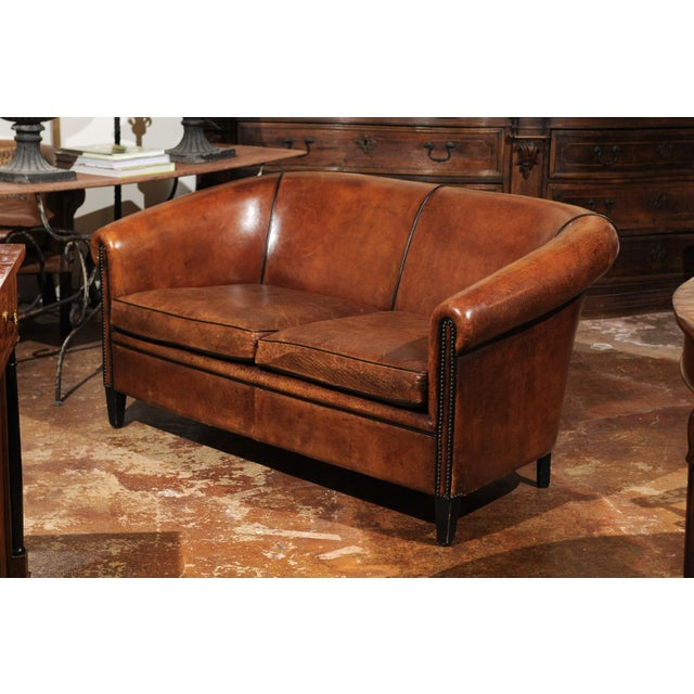 A French brown leather sofa from the early 20th century with nailhead trim. Attracting our eye with its handsome...