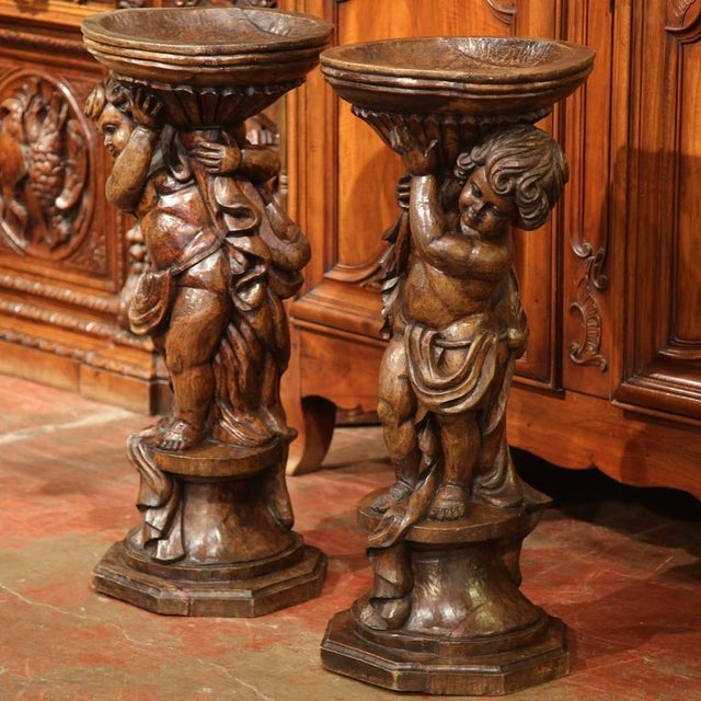 Elegant pair of antique carved planters from France, circa 1790, featuring a pair of cherubs holding jardiniere bowls....