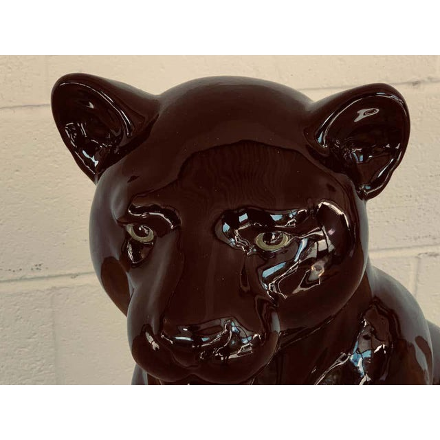"""Pair of Italian porcelain seated black panthers, each one realistically modeled, with green eyes. Stamped """"Made in Italy""""..."""