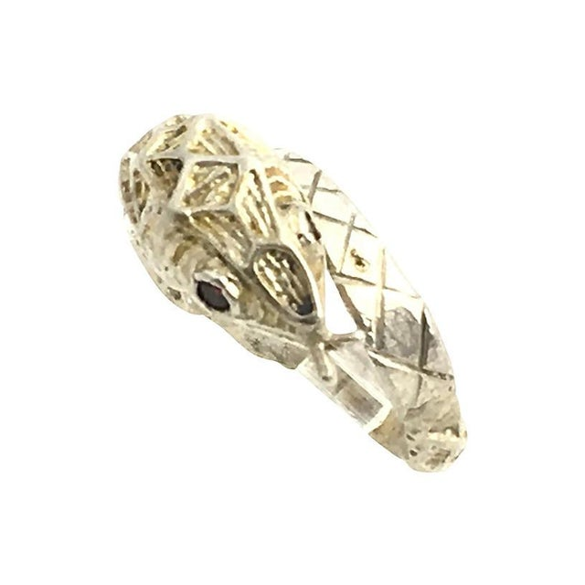 Etched sterling silver snake ring set with garnet eyes. Size: 7.5. COLOR: red/silver CONDITION: Very Good; age wear...