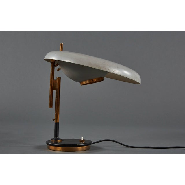 An adjustable Oscar Torlasco table lamp for Lumi in painted metal and brass with a glass lens.