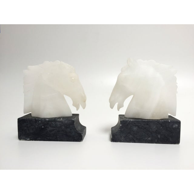 Lovely vintage pair of alabaster and dark stone horse head bookends. Good condition. One horse's ears have been chipped off.