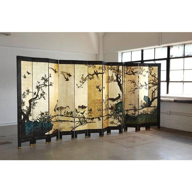 Impressive, large, 12-panel double sided hand-painted, hand-carved Coromandel screen. The gilded side is showing a...