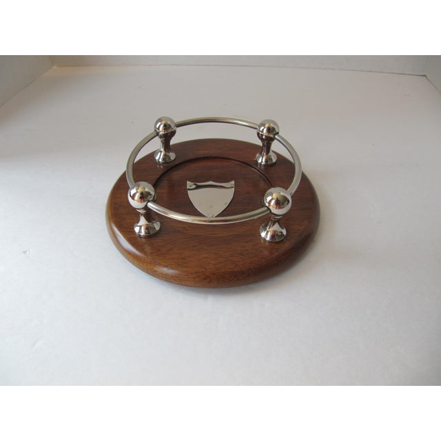 Beautiful wood wine coaster with chrome details and a crest in the center.