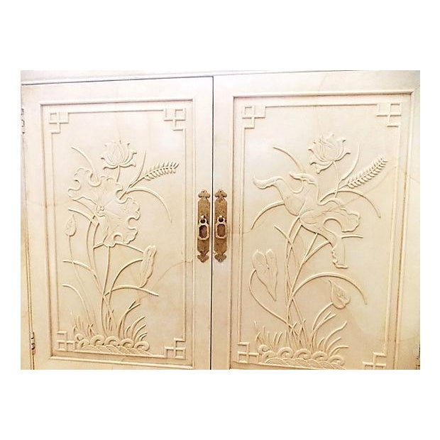 White lacquered Asian-style server/bar cabinet with raised floral design on front doors. Doors have gilded metal pulls...