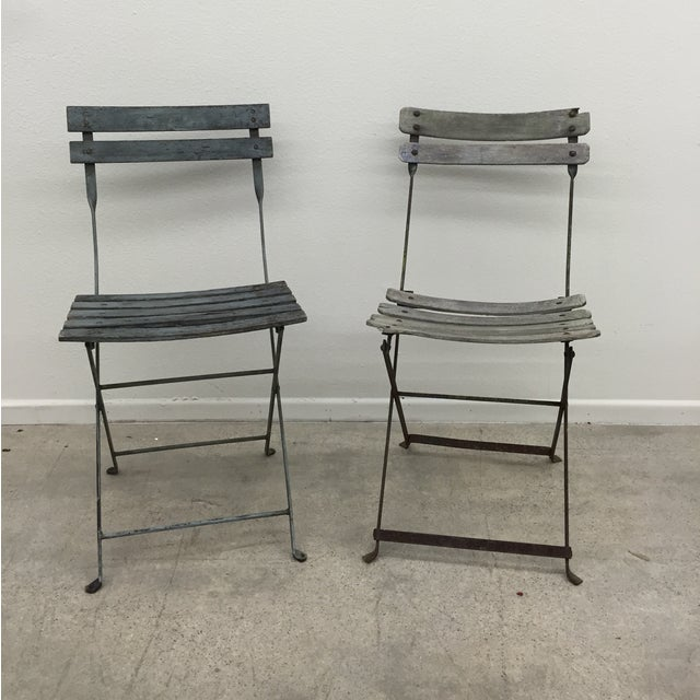 A pair of French metal base, wooden slat garden chairs. Original paint. Chairs fold up. Slats are in overall good...